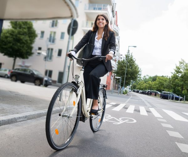 Smiling Young Businesswoman With Handbag Riding Bicycle On Street